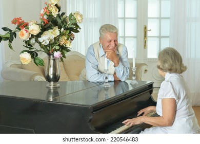 Senior woman playing the piano at home with her husband