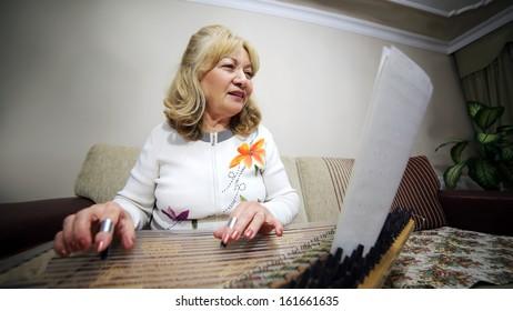 Senior woman playing qanun, turkish string instrument, while husband listening
