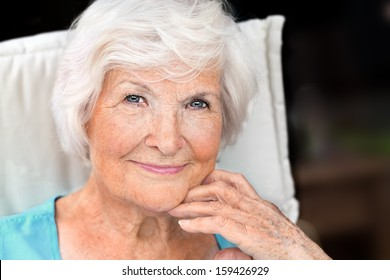 Senior woman portrait, looking relaxed with hand on chin