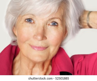 Senior woman portrait  with white hair and  red blouse, holding left arm on the side and has the hand in her hair