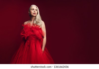 Senior woman posing confidently in a red gown. Mid adult looking glamorous in red dress over red background.