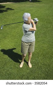 Senior woman practicing golf