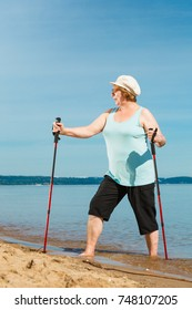 Senior woman practicing nordic walking on sea shore, Active elderly female enjoying sunny summer day. Healthy lifestyle in old age.