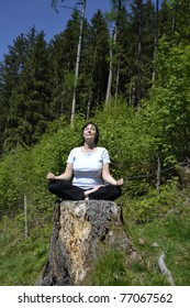 Senior woman practicing yoga in the forest.