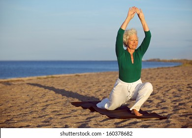 Senior woman practicing yoga poses on the sandy beach. Elder caucasian woman stretching legs and arms on the seashore. Healthy lifestyle and fitness concept
