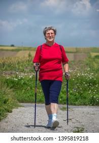 Senior woman practising nordic walking in the countryside
