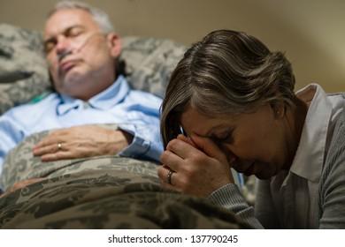 Senior woman praying for sick man sleeping in hospital bed