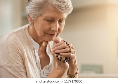 Senior woman praying while holding christian symbol of crucifix. Old woman praying to god with hope and closed eyes. Elderly believer make a prayer with faith holding rosary in hands.