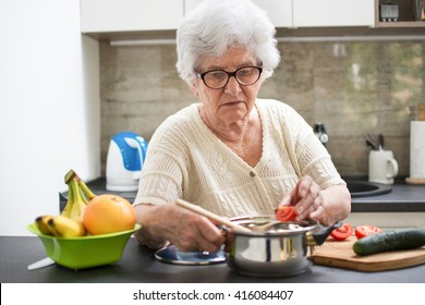 Senior woman preparing a meal with vegetables in the kitchen.