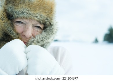 Senior woman pulling flaps of fur hat over face, in snowy landscape, close-up