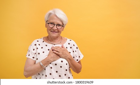 Senior woman putting her hands over the heat with smile. Emotions isolated on orange background. High quality photo