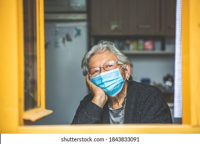 Senior woman quarantined by coronavirus, covid-2019 at home, looking outside by the windown, stay at home