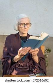 Senior woman reading a blue book outdoors