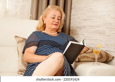 Senior woman reading a book ,at living room