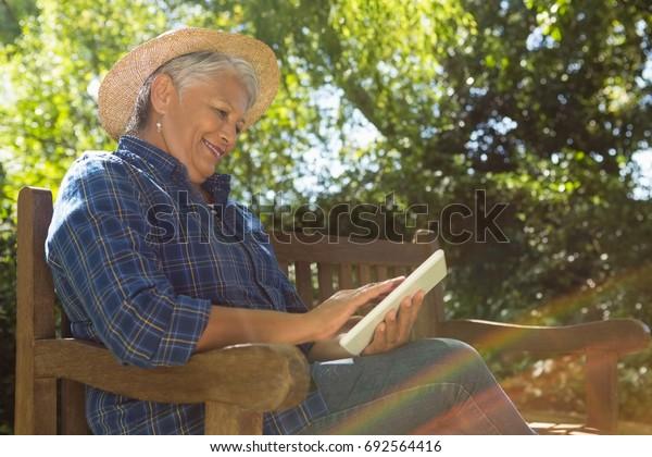 Senior woman reading book in the garden