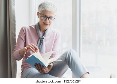 Senior woman reading book in her bright apartment, Education and learning concept