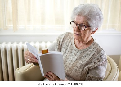Senior woman reading book at home.