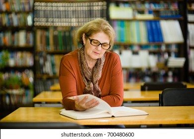 Senior woman reading book in library