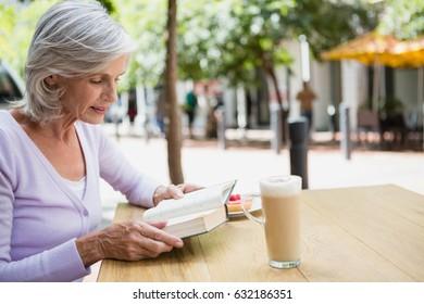 Senior woman reading a book in outdoor café