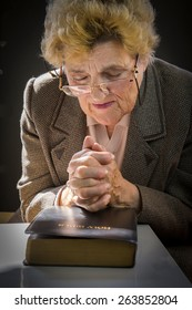 Senior woman reading holly bible and praying. Woman with glasses