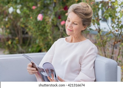 Senior woman reading a magazine sitting on a couch outdoor. Happy elderly woman reading a gossip magazine in her free time. Mature woman relaxing in the garden.