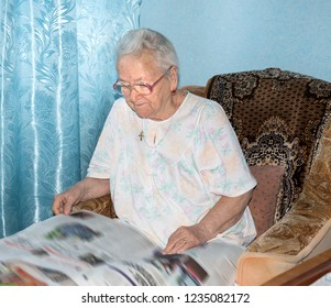 Senior woman reading morning newspaper at home