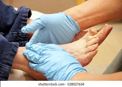 Senior woman receives foot examination from gloved podiatrist. Horizontal.
