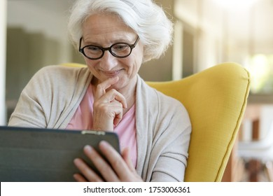 Senior woman relaxing in armchair and using digital tablet