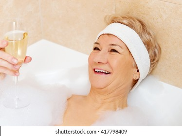 Senior woman relaxing in bath with glass of champagne