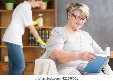 Senior woman relaxing with book, professional caregiver doing housework