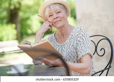 Senior woman relaxing in garden and reading book
