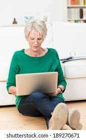 Senior woman relaxing at home with a laptop computer sitting on the hardwood floor in the living room with her back to the sofa concentrating on her work