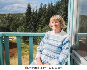 Senior woman relaxing at the house balcony. Serious woman is looking at view.