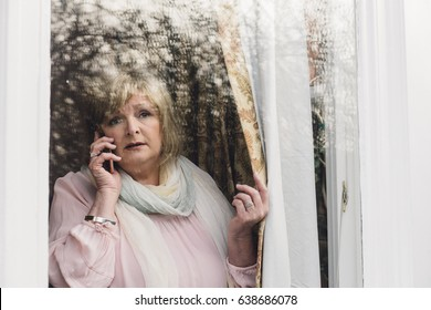 Senior woman is reporting a neighborhood crime to the police on the phone. She is looking out her window.
