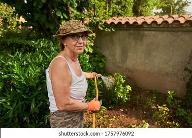 Senior woman in retirement working in the garden loking in camera