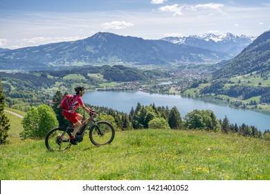 senior woman riding her electric mountain bike in springtimeon the mountains above the Alpsee near Immenstadt, Allgau,Bavaria, Germany