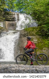 senior woman, riding her electric mountain bike and watching a cascade in the Allgau Alps near Oberstaufen, Bavaria, Gemany