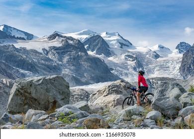 Senior woman, riding her e-mountain bike on the trail to the Morteratsch glacier near Pontresina , Engadin, Switzerland,Alps. In the background the famous mountains of Piz palu, Bellavista, Bernina