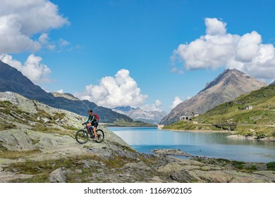 senior woman, riding her e-mountainbike on the famous Bernina express trail at Lago Bianco, Bernina Pass near Pontresina an St.Moritz, Engadin, Switzerland