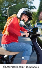 Senior woman riding her scooter crouching low over the handlebars in her safety helmet laughing as she rides down the street