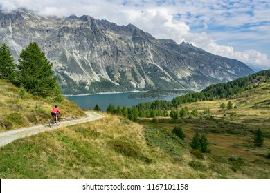 Senior woman, riding here e-mountain bike on the famous trails around the lakes in the upper Engadin, between Saint Moritz and Maloja, Engadin, Switzerland with stunning views on the lake of Silvaplan