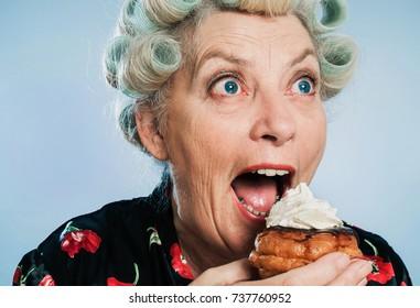 Senior Woman with Rollers in her Hair, indulging in her Guilty pleasure of eating too many cakes / Sweets: Taking a BIG bite