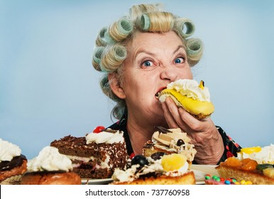 Senior Woman with Rollers in her Hair, indulging in her Guilty pleasure of eating too many cakes / Sweets