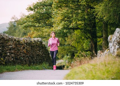Senior woman is running along a trac path in the Lake District with a water bottle.