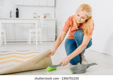 Senior woman with scoop and brush cleaning floor under carpet