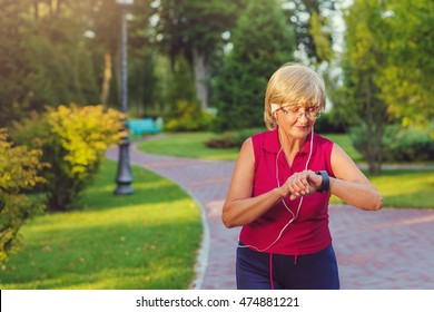 Senior woman setting up the fitness smart watch for running and checking watch device