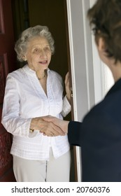 Senior woman shaking hands at her front door