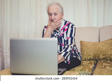 Senior woman shocked with something on laptop screen