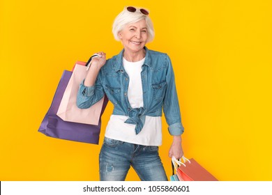 Senior woman shopper studio isolated on yellow wall wearing sunglasses carry bags