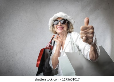 Senior woman with shopping bags showing OK.
